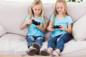 shutterstock_145610965 Cute twins playing video games together in the living room Copyright by Shutterstock.com