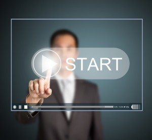 business man pressing start button to play video clip shutterstock_99799703