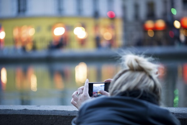 Woman using smartphone to photograph city scene (Quelle: Instagram)