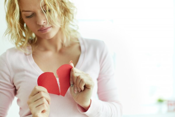 shutterstock_147026843 Sad female tearing up red broken paper heart