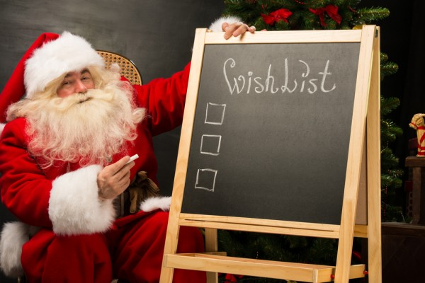 copyright by shutterstock_160222442 Santa Claus sitting near chalkboard with wishlist sign and blank copy space for checkboxes and your text