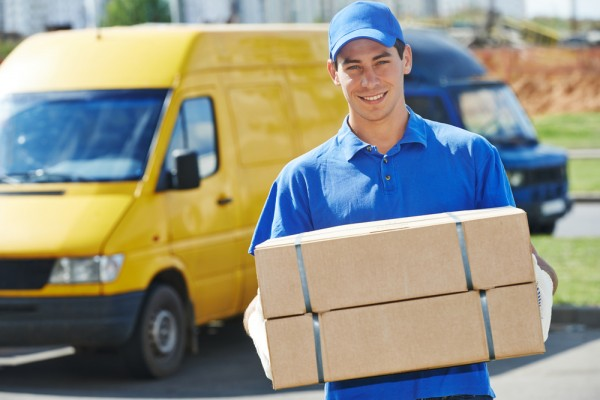 Smiling young male postal delivery courier man in front of cargo van delivering package shutterstock_151595867