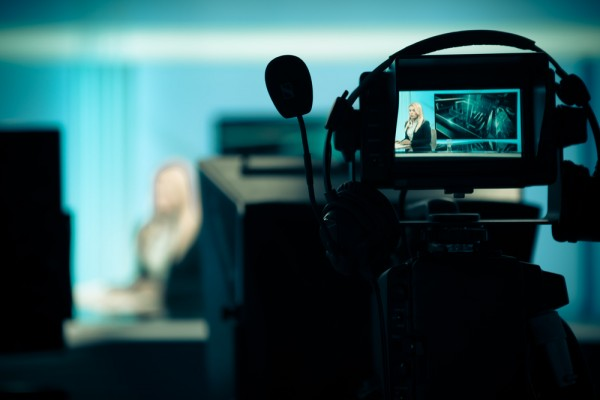Young beautiful blonde television announcer at studio during live broadcasting.Female TV director at editor in studio.Recording at TV studio with television anchorwoman. TV NEWS studio with camera shutterstock_237214225