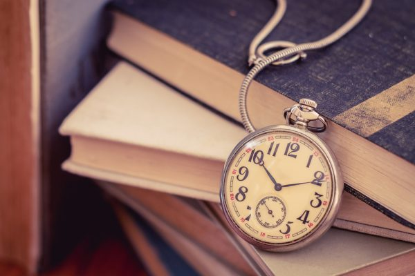 shutterstock_380335285 Old pocket watch on stack of books, time to read