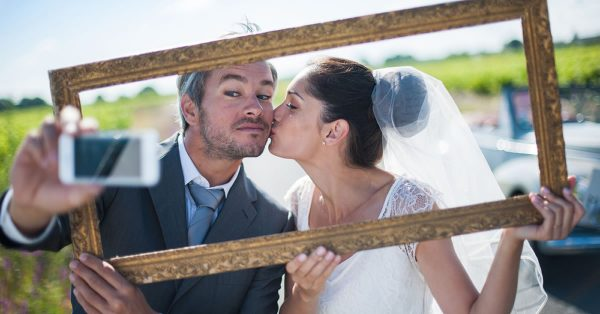 a lovely couple is taking funny selfies for their wedding, taking a frame in front of their faces, behind them a lovely country road by shutterstock.com